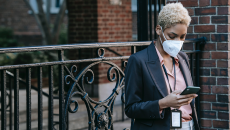 Woman in mask checks smartphone for update