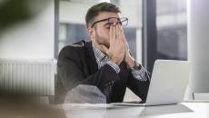 worker rubbing eyes at laptop