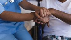 Nurse holding hands of patients.