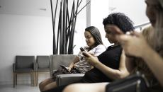 Women in waiting room on mobile phones.