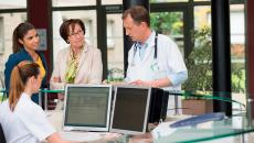 Doctor talking to mother and daughter at reception desk