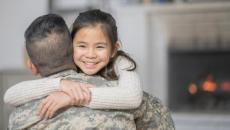 A person wearing military fatigues hugs a child.