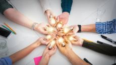 Circle of hands holding lightbulbs