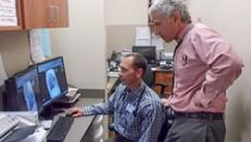 Dr. Billy Oley, left, and Dr. William George review an electronic medical record
