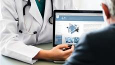 Doctor showing patient a laptop.