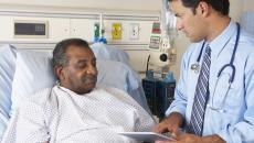 doctor using tablet with hospital patient