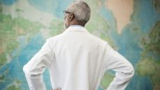 Doctor looking at a world map