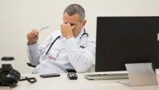 Person in white coat, frustrated in front of computer