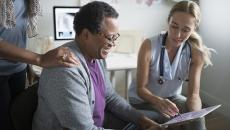 hospital doctor talking to patient with EHR tablet