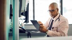 A doctor looks at a tablet