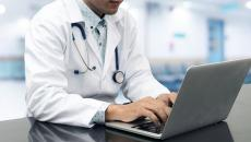 A person with a stethoscope using an EHR on a computer