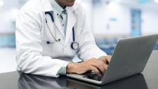 A person wearing a stethoscope on a computer