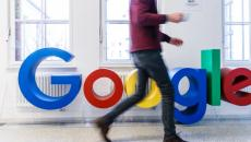 A person walks by the Google logo