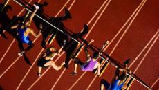 runners jumping hurdles