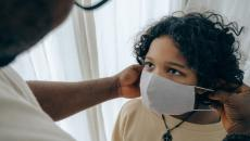 An adult puts a mask on a child