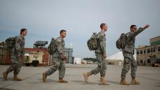 US military troops walking across airfield