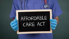 Doc holding ACA sign