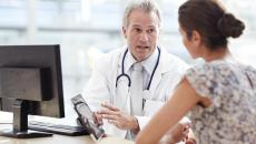 doctor talking with patient at hospital about EHR