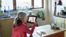 A person sits at a table speaking with a doctor via tablet.