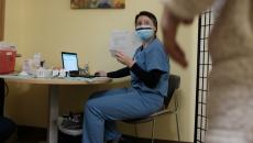 A person in scrubs and personal protective equipment sits at a computer