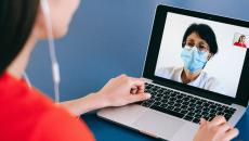A patient speaks with a doctor via laptop