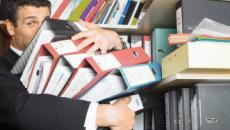 Man holding large pile of binders