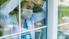 doctor in mask looking out window