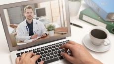 A doctor in a white coat on a computer screen