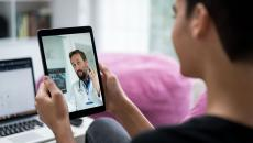 A person using a tablet for a video call with a doctor.