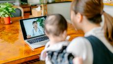 A person with a baby uses video telemedicine at a laptop