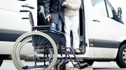 elderly getting out of van and into a wheelchair