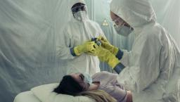 Doctors in Hazmat suits treating patient.