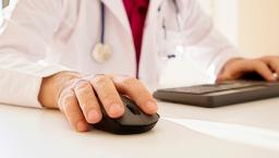A person with a stethoscope around their neck clicks a computer mouse