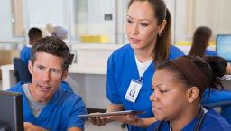 Three hospital staff members at a computer screen