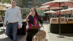 blind woman using Microsoft app Soundscape on city street with her guide dog