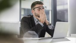 worker rubbing eyes at laptop