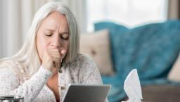 Woman coughing and using telehealth