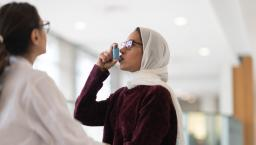 A patient uses an inhaler for asthma while a person in medical wear watches.