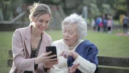 A younger person shows an older person something on the phone