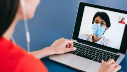 A telehealth professional on laptop screen with user
