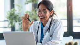 A doctor waves at a laptop screen