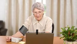 Senior using telemedicine blood pressure cuff.
