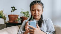 A person in braids browses on the phone