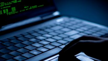 A shadowy hand at a blue-tinted laptop