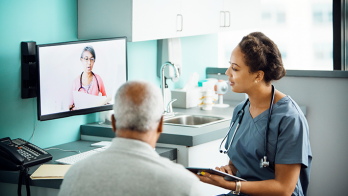 Patient with one medical professional in an office and another on-screen