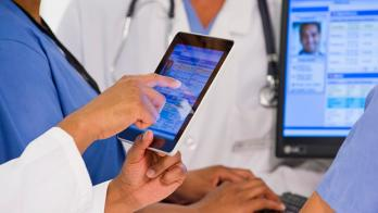 A doctor points at an EHR on a tablet