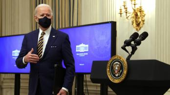 President Joe Biden stands in front of monitors
