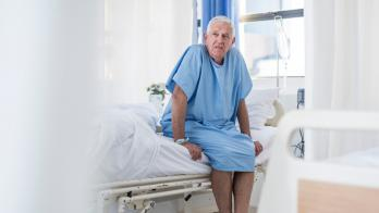An older man seated on a hospital bed