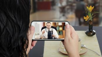 A person holding a mobile phone with a person wearing a stethoscope on screen