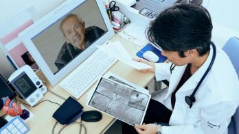 A doctor examines coronary images while a patient is on video screen